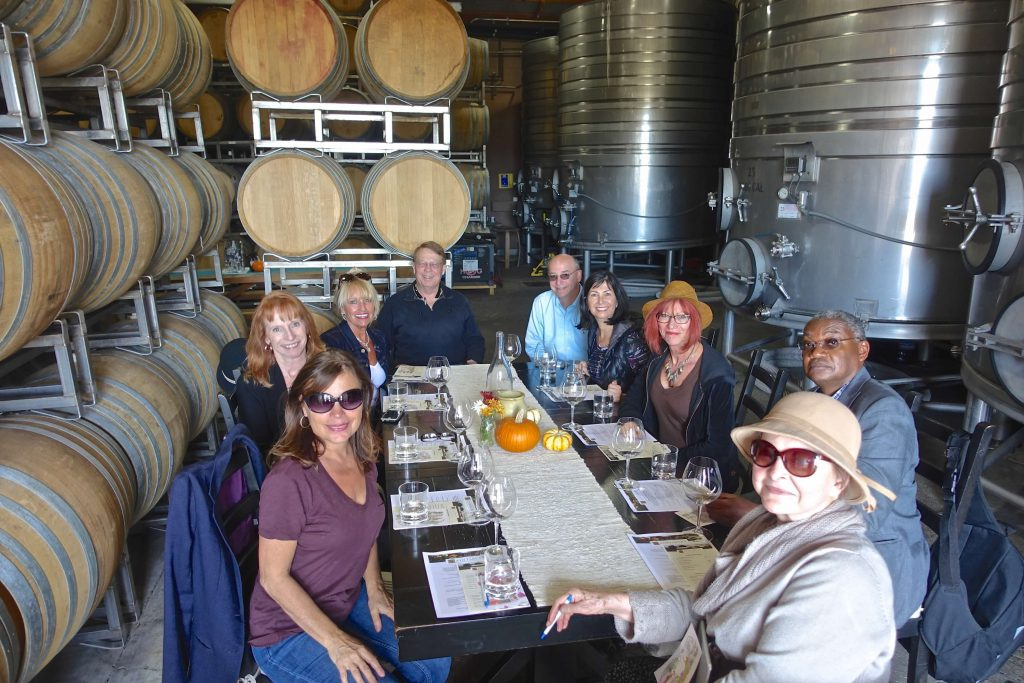 group of people sitting at a table for wine tasting