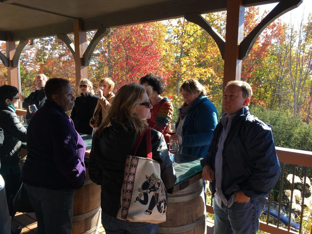 group tasting with fall leaves in background